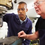 Engineer Teaching Apprentice To Use Milling Machine